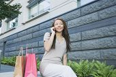 African woman with shopping bags talking on cell phone