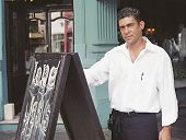 Hispanic waiter next to chalkboard in front of restaurant