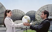 Hispanic businesspeople holding globe in front of satellite dishes