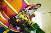 picture of carnival ride  - Teenage Hispanic couple sitting in teacup carnival ride - JPG