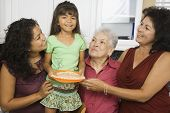 Multi-generational Hispanic female family members smiling in kitchen