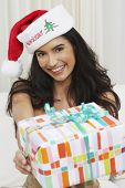 Hispanic woman wearing Santa hat and holding out gift