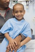 stock photo of hospital gown  - African boy in hospital gown sitting on father - JPG