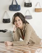 Hispanic businesswoman behind counter at boutique