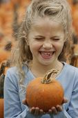 Girl laughing and holding pumpkin