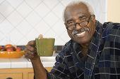 Senior African man holding coffee mug