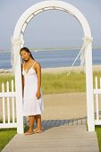 Asian woman in archway at beach