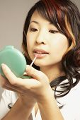 Asian woman applying lip gloss
