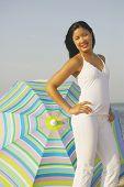 Hispanic woman next to beach umbrella