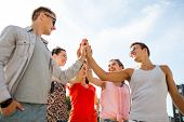 friendship, leisure, summer, gesturer and people concept - group of smiling friends making high five outdoors