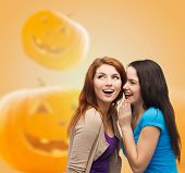 happiness, holidays, firendship and people concept - smiling teenage girls gossiping over halloween pumpkins background