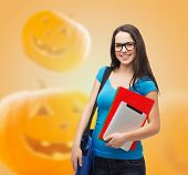 education, holidays, school and people concept - smiling student girl in glasses with books and bag over halloween pumpkins background
