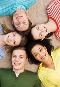 education and happiness concept - group of young smiling people lying down on floor in circle