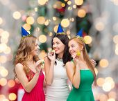 holidays, people and celebration concept - smiling women in party caps blowing to whistles over chri