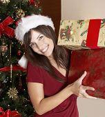 Hispanic woman holding Christmas gifts