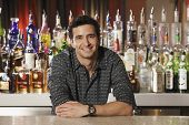 Hispanic male bartender leaning on bar
