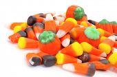 a pile of different Halloween candies on a white background