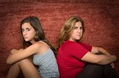 Teenager problems - Angry teenage girl and her worried mother sitting back to back