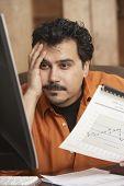 Hispanic businessman holding graph