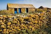 Old stone farm covered with yellow lichen in Quemenes island, Brittany, France