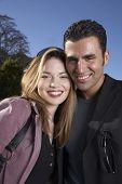 Hispanic couple hugging outdoors