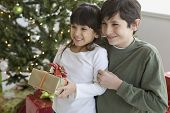 Hispanic brother and sister holding Christmas gift