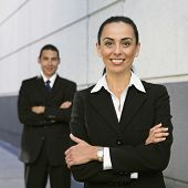 Hispanic businesswoman with coworker in background