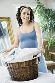 Pregnant African woman holding laundry basket