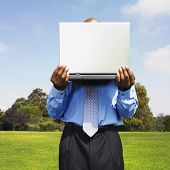 African businessman holding laptop in field