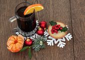 Christmas mulled wine with mince pie, red bauble decorations and winter flora over oak background.
