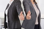 Close-up of female business team holding their thumbs up