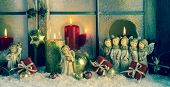 Atmospheric classic christmas decoration with angels, presents and red candles.