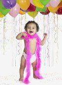 African baby wearing feather boa at party