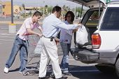 Hispanic family loading groceries into car