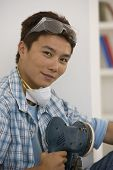Asian man holding power sander