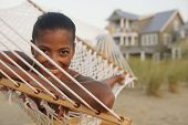 African woman laying in hammock at beach