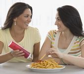 Two young women eating french fries