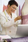 Asian female clothing designer using dress dummy
