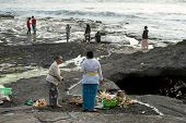 SEPTEMBER 17, 2014, BALI, INDONESIA: Balinese Hindu devotees pray at sunset on the rocky beaches around the Tanah Lot Temple. Bali Island is an important tourist destination in the world.