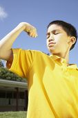 Asian boy flexing muscles