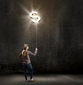 Young woman in casual holding balloon shaped like dollar