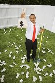 Mixed Race businessman raking up money
