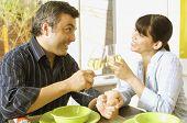 Hispanic couple toasting with wine