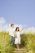 Asian couple waving in field