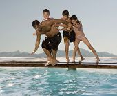 picture of pre-adolescent child  - Hispanic children pushing father into swimming pool - JPG