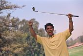 Hispanic man cheering with golf club