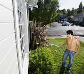 Bare-chested Hispanic man watering plants