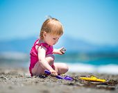 pic of shoulder-blade  - cute baby girl playing in the sand with a shovel on the beach on a beautiful summer day - JPG