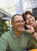 Hispanic couple listening to cell phone