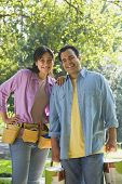 Hispanic couple with tool belt and paint cans